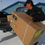 Photo: Dominic carries a new drum kit, still in its box, to his pickup truck.