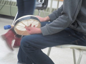 Photo: Student, seated, holding traditional hand drum.