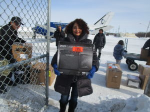 Photo: Rosy at Attawapiskat airport carrying an amplifier from plane to truck.